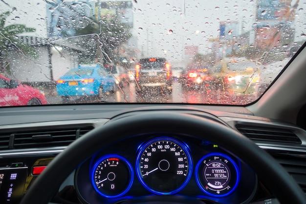 Stau in der hauptverkehrszeit. hand eines fahrenden autos mit stau in der regenzeit. regenwetter im straßenverkehr