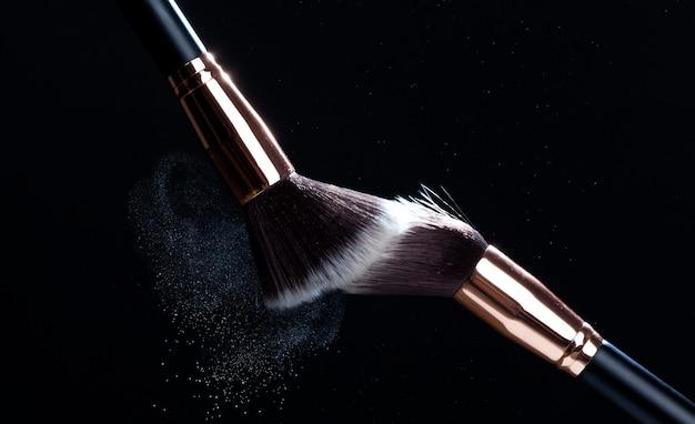 Staub von kosmetischem puder zusammen mit kosmetischen bürsten, staub von puder wird um die bürsten verteilt