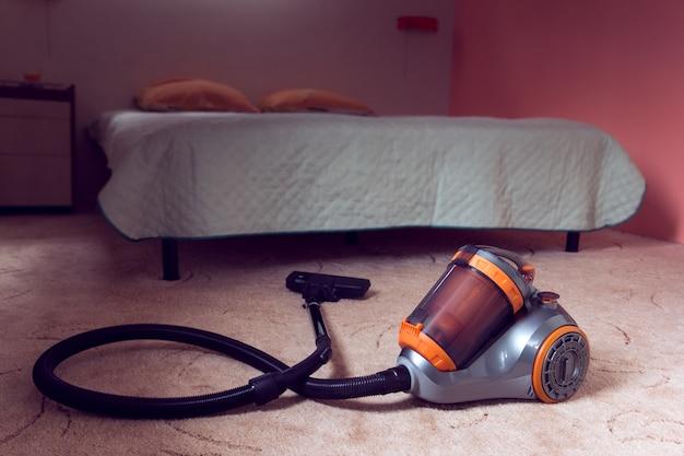 Staubsauger auf einem schlafzimmerhintergrund