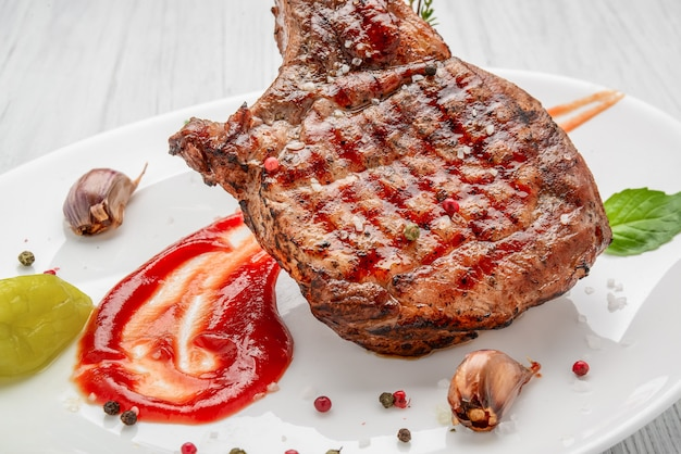 Steak am knochen. tomahawk steak auf einem weißen holztisch. draufsicht.