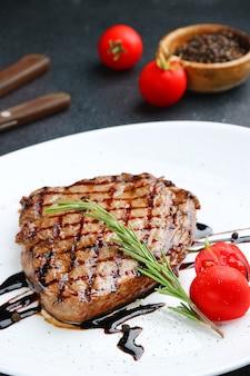 Steak auf weißem teller mit kirschtomate und rosmarin hautnah
