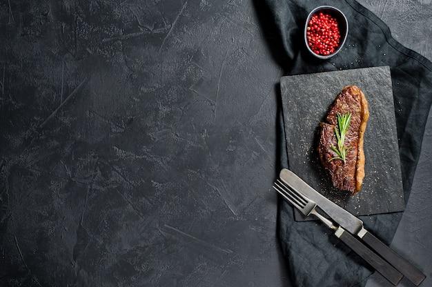 Steak aus marmoriertem rindfleisch schwarz angus braten hinten. copyspace