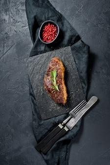 Steak aus marmoriertem rindfleisch schwarz angus braten hinten.