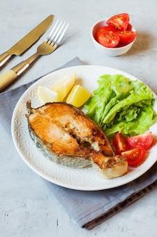 Steak backte lachsfische auf einer platte mit frischgemüse.