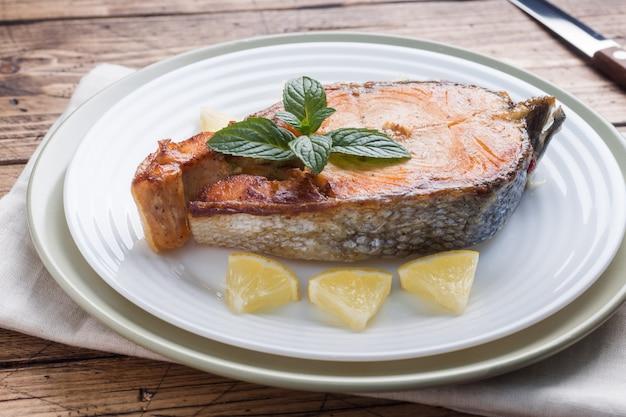 Steak gebackener fischlachs auf einer platte mit zitrone. holztisch.