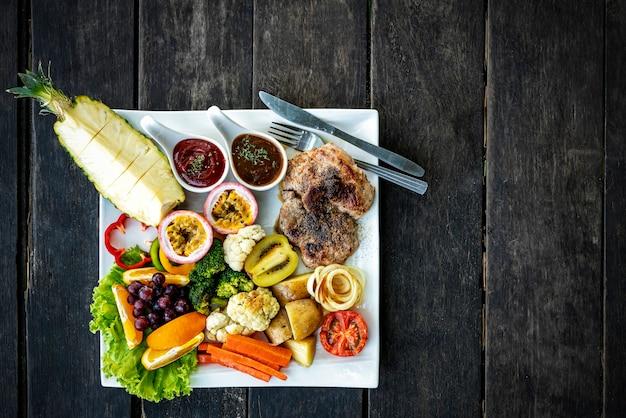 Steak mit einer mischung aus gesundem gemüse und obst auf dem teller. essen auf dem tisch mit freiem platz.