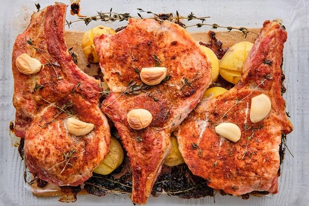 Steak mit knochen und kartoffeln im ofen in einer bratpfanne mit knoblauch und thymian gebacken