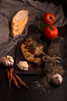 Steak, tomate, petersilie, knoblauch und kartoffelpüree auf schwarzem holz und stoff.