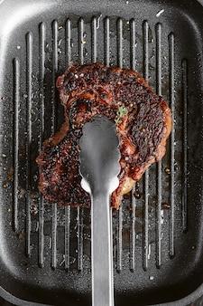 Steak von einem frischen stück marmorrindfleisch in einer pfanne gebraten