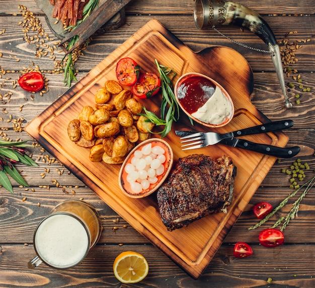 Steakbrett mit fleisch, kartoffeln und soßen.
