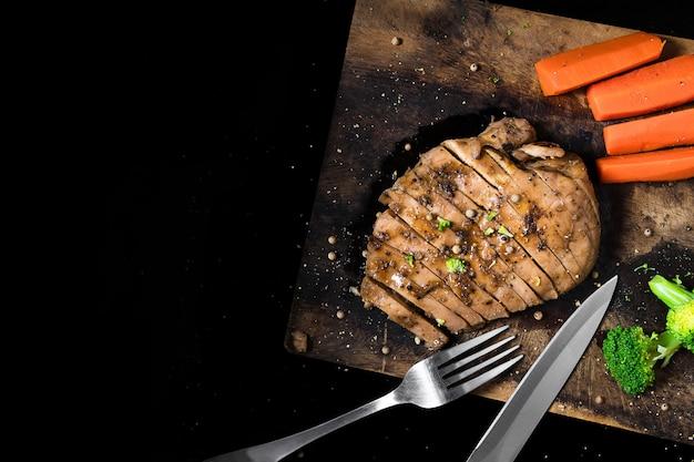 Steakchickenkarotten und -brokkoli auf einem schneidebrett