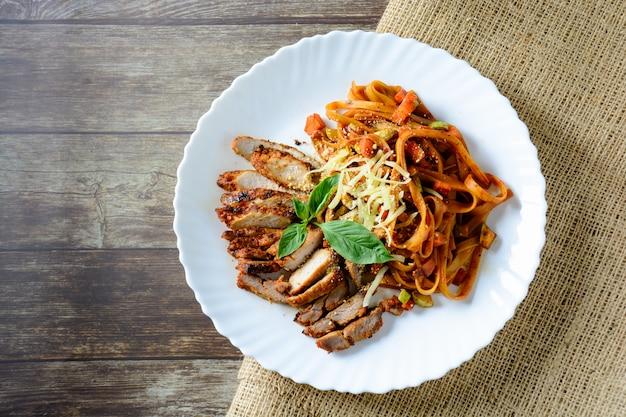 Steakfleisch mit spaghettis und käse auf holz
