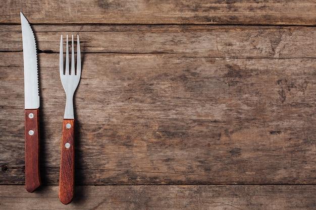 Steakgabel und -messer auf hölzernem hintergrund