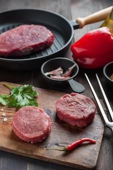 Steaks auf schneidebrett, fertig zum kochen. frisches rohes fleisch, hölzerner hintergrund, selektiver fokus