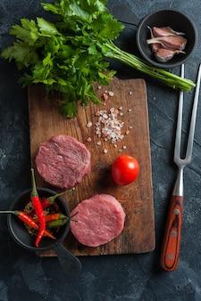 Steaks auf schneidebrett, fertig zum kochen. frisches rohes fleisch, hölzerner hintergrund, y