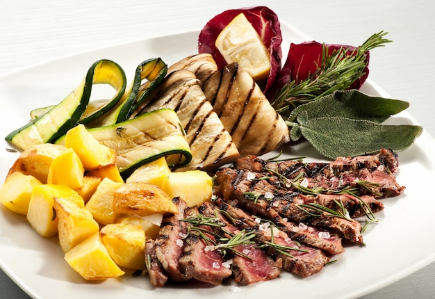 Steakscheiben mit kartoffeln, auberginen und kürbis