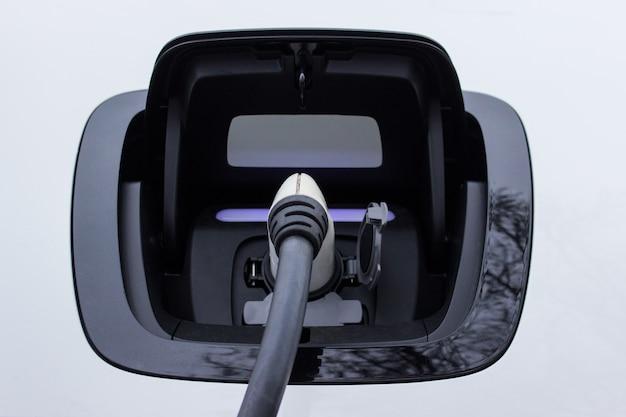 Steckdose eines elektroautos mit angeschlossenem ladegerät