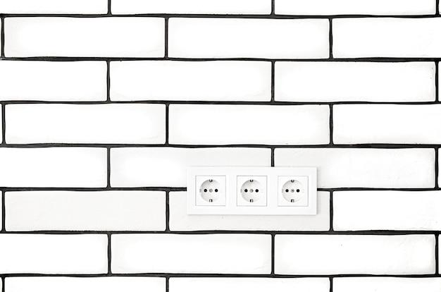 Steckdosen gegen eine weiße backsteinmauer.