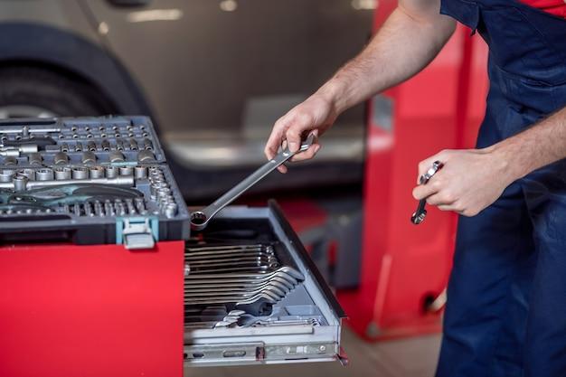 Steckschlüssel. hände des automechanikers in blauen overalls mit schraubenschlüsseln in der nähe des offenen werkzeugkastens, sein gesicht ist nicht sichtbar