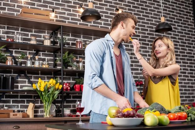 Stehen in der nähe von frau. bärtiger gutaussehender fürsorglicher ehemann, der gemüse für salat schneidet, der in der nähe von frau steht