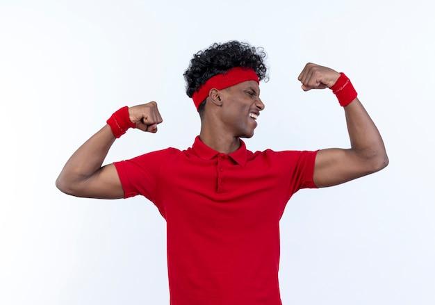 Stehen in der profilansicht freudiger junger afroamerikanischer sportlicher mann, der stirnband und armband tut und starke geste lokalisiert auf weißem hintergrund tut