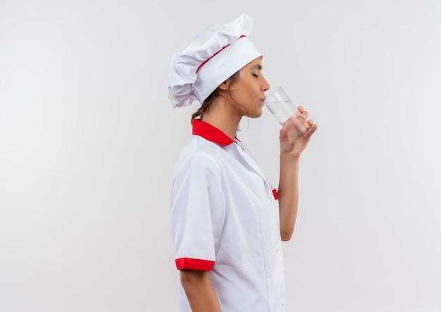 Stehen in der profilansicht junge köchin, die kochuniform trägt, trank wasser aus glas mit kopienraum