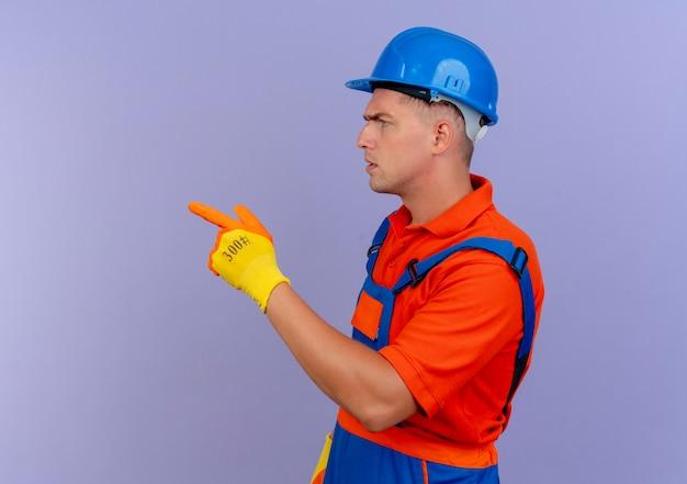 Stehen in der profilansicht junger männlicher baumeister, der uniform und schutzhelm in handschuhen trägt, zeigen auf lila seite