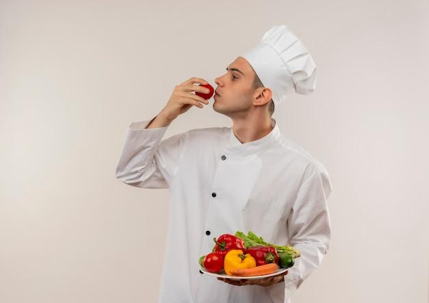 Stehen in der profilansicht junger männlicher koch, der kochuniform trägt, die gemüse auf teller hält und tomate in seiner hand mit kopienraum schnüffelt