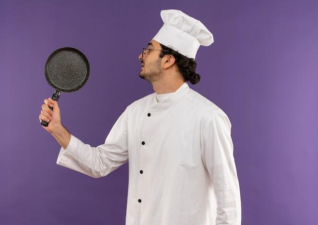 Stehen in der profilansicht junger männlicher koch, der kochuniform und gläser hält und die bratpfanne auf lila hält