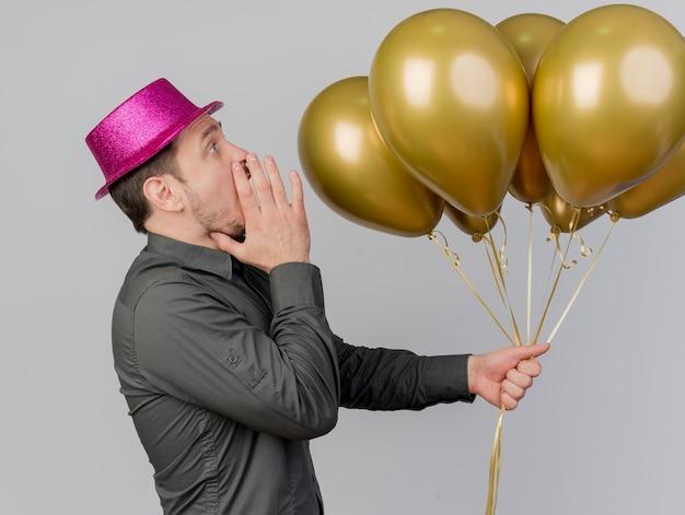 Stehen in der profilansicht junger party-typ, der rosa hut hält, der ballons hält, die jemanden lokalisiert auf weiß nennen
