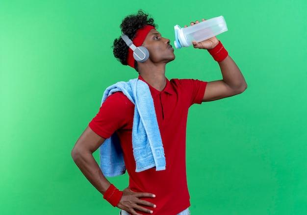 Stehen in der profilansicht junger sportlicher mann, der stirnband trägt
