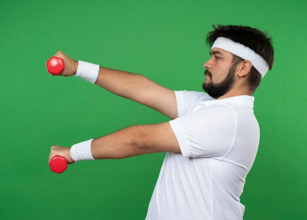 Stehen in der profilansicht junger sportlicher mann, der stirnband und armband trägt, die mit hanteln, die auf grüner wand lokalisiert werden
