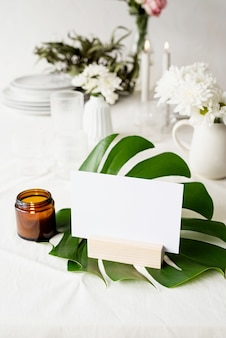Stehen sie für broschüren mit weißem papier, hölzerner zeltkarte auf monstera-blatt auf restauranttisch