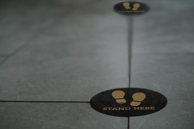 Stehen sie hier fußzeichen oder symbol auf dem boden im café Premium Fotos