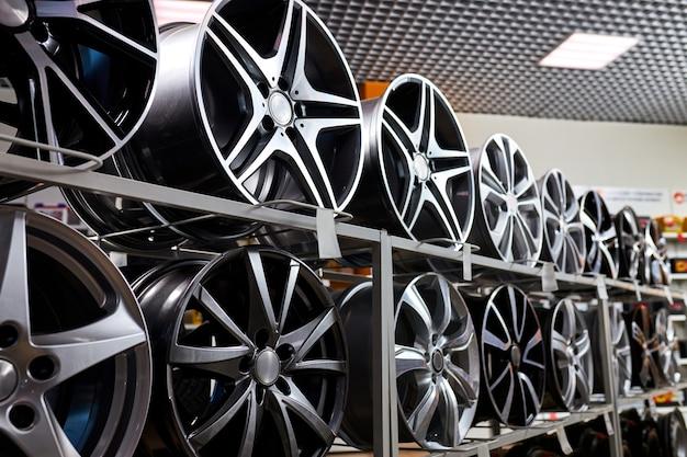 Stehen sie mit leichtmetallrädern im modernen reifengeschäft, nahaufnahmefoto von auto-rädern im auto-service-shop