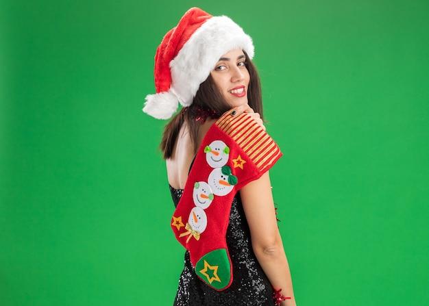 Stehend hinter ansicht lächelndes junges schönes mädchen, das weihnachtsmütze mit girlande am hals hält weihnachtssocke auf schulter lokalisiert auf grüner wand mit kopienraum