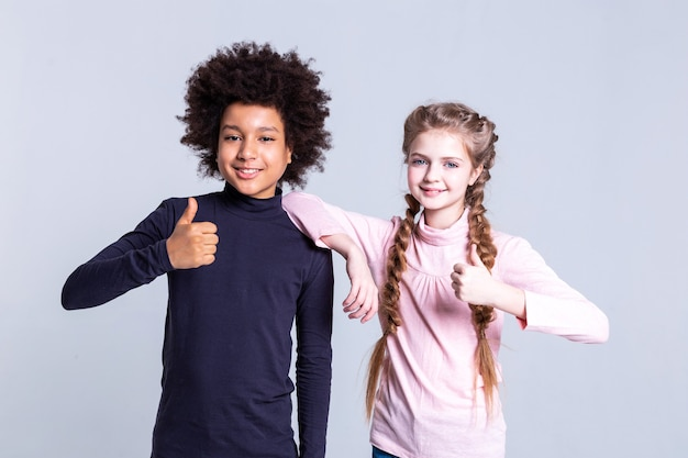 Stehend in der nähe von mädchen. fröhliche süße kinder, die als models für professionelle fotoshootings arbeiten und ihre miniaturansichten vor der kamera zeigen
