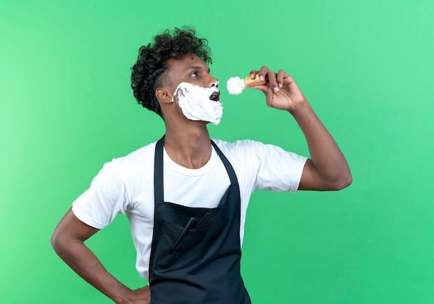 Stehend in der profilansicht junger afroamerikanischer männlicher friseur in uniform mit rasierschaum auf seinem gesicht, der rasierpinsel hält und singt