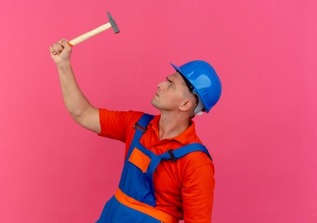 Stehend in der profilansicht junger männlicher baumeister, der uniform und schutzhelm trägt und den hammer anhebt und betrachtet