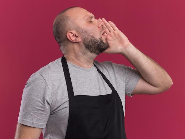 Stehend in der profilansicht mit geschlossenen augen slawischer männlicher friseur mittleren alters in uniform, die jemanden lokalisiert auf rosa wand ruft