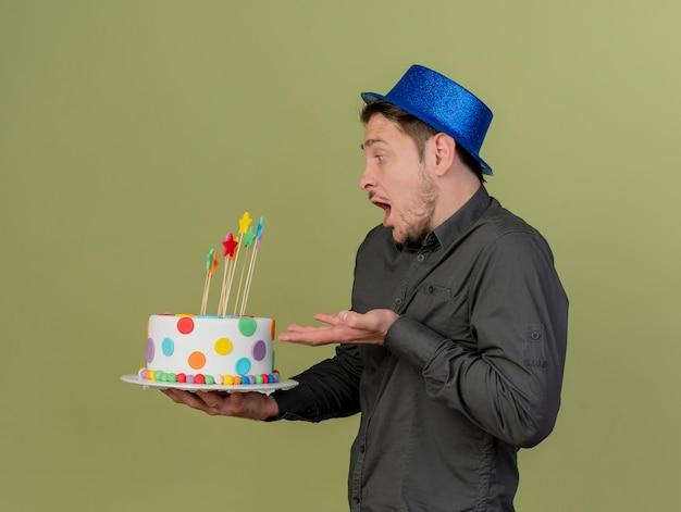 Stehend in der profilansicht überraschte junger party-typ, der schwarzes hemd und blauen hut hält und punkte mit hand an kuchen lokalisiert auf olivgrün trägt