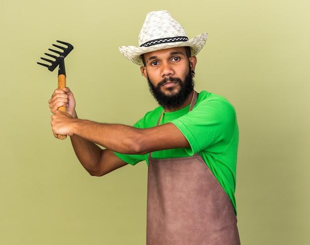 Stehend in kampfpose junger gärtner afroamerikanischer mann mit gartenhut mit rechen