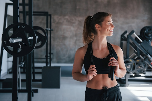Stehend mit springseil in den händen. wunderschöne blonde frau im fitnessstudio zu ihrer wochenendzeit