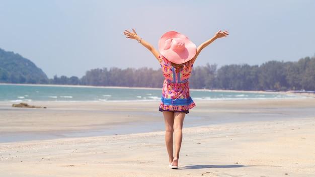 Stehende arme der freiheitsfrau streckten zurück aus und genießen das leben auf dem strand