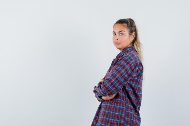 Stehende arme der jungen frau verschränkt, während sie in kariertem hemd über die schulter schauen und hübsch aussehen