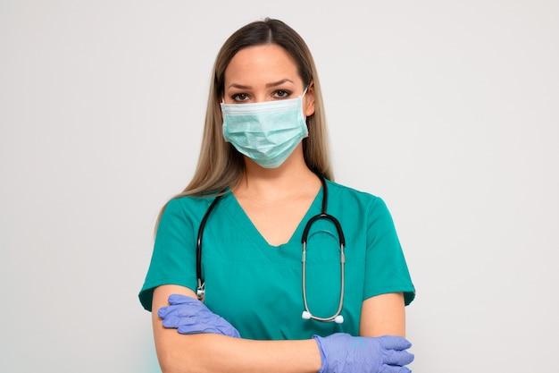 Stehende arme der weiblichen krankenschwester verschränkt mit medizinischer maske