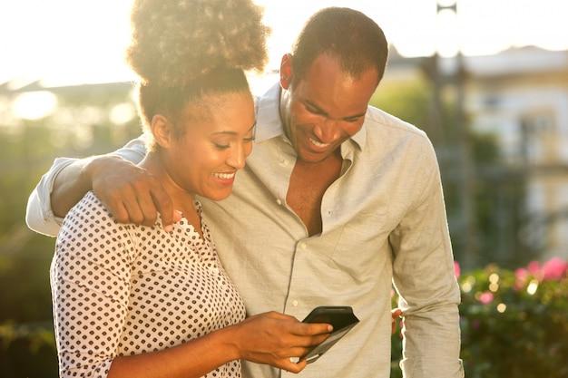 Stehende außenseite des glücklichen paars, die mitteilung auf telefon betrachtet