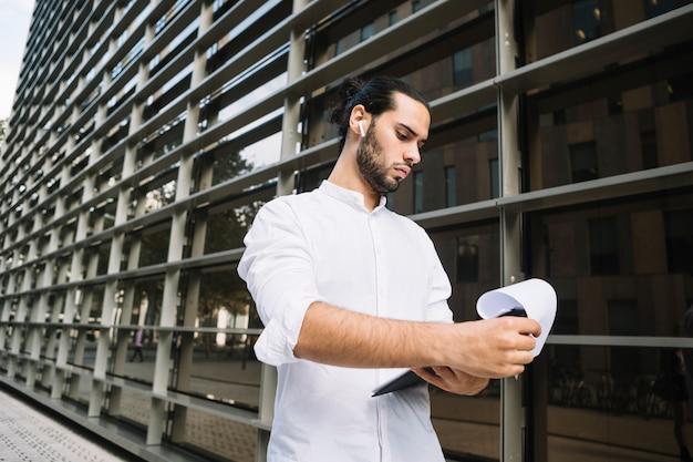 Stehende außenseite des hübschen geschäftsmannes das unternehmensgebäude, das dokumente auf klemmbrett betrachtet