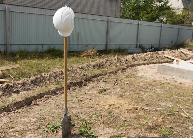 Stehende bauschaufel mit weißem ingenieur-kopfschutz am boden am projektstandort.