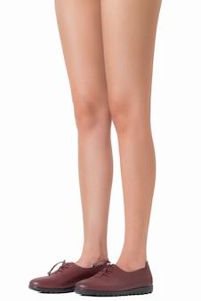 Stehende beine der seitenansicht der schönen langen beine der frau werfen die tragenden lederschuhe auf, die auf weiß lokalisiert werden